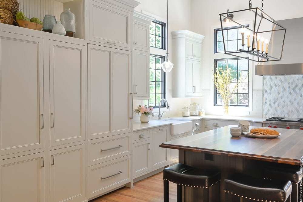white kitchen remodel with wood tops and metal hood