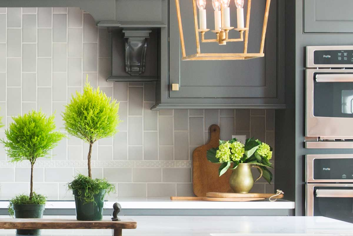 This space was transformed from dark & gloomy to now happily welcoming everyone. Charcoal colored cabinets and the light aluminum tile backsplash create an elegant pairing.