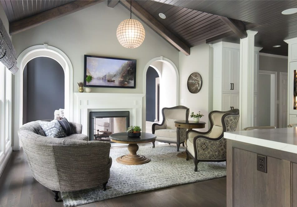 The round geometric designed pendant and dark stained wood shiplap ceiling in the sitting area, adjoined to the kitchen is unexpectedly perfect. It's all about mixing bold motifs, shapes, and finishes and warming them with wood finishes.
